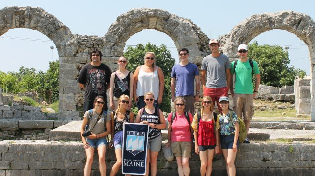 students standing in front of ancient ruins