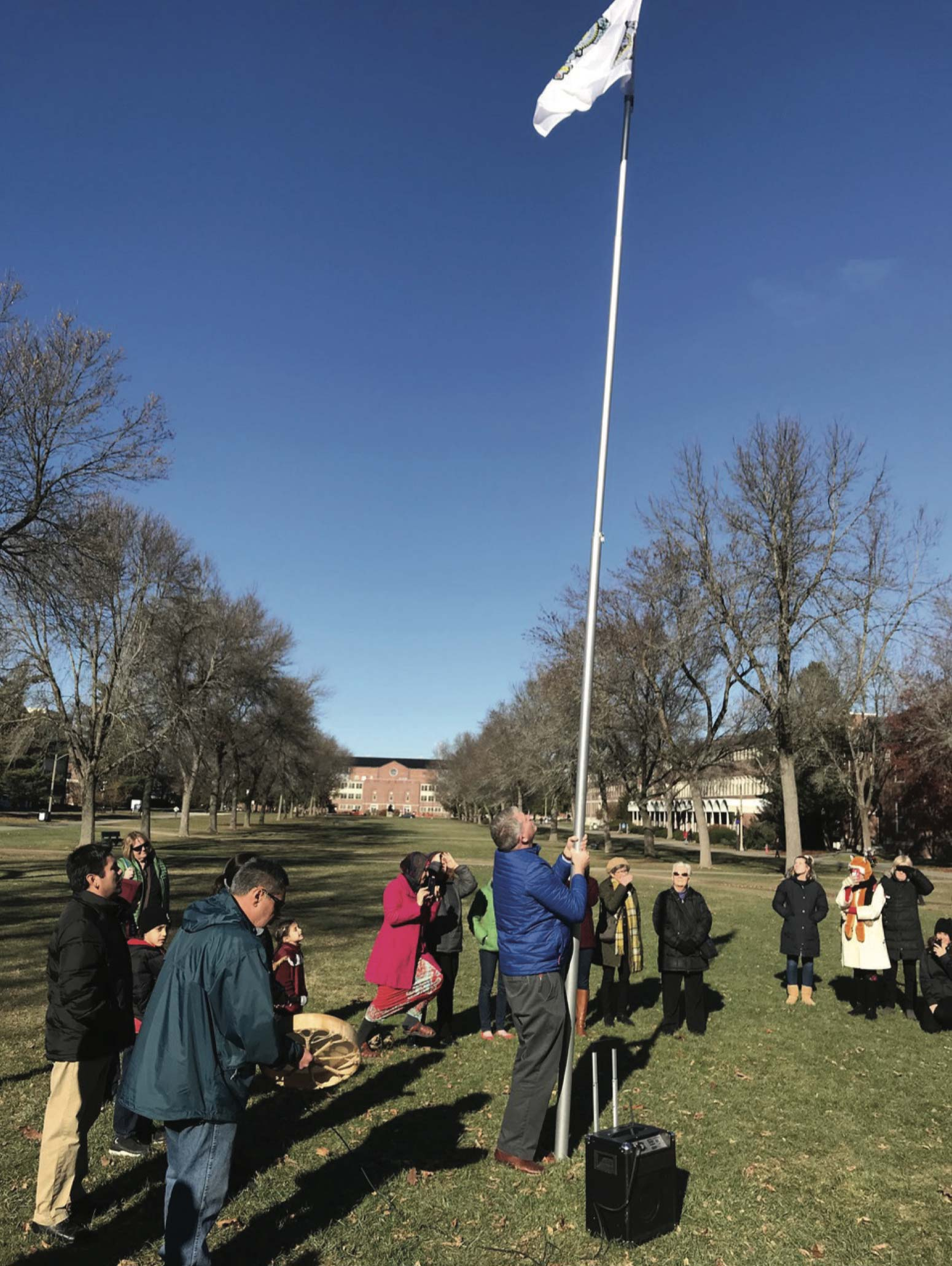 Photo of people raising the Penobscot flag