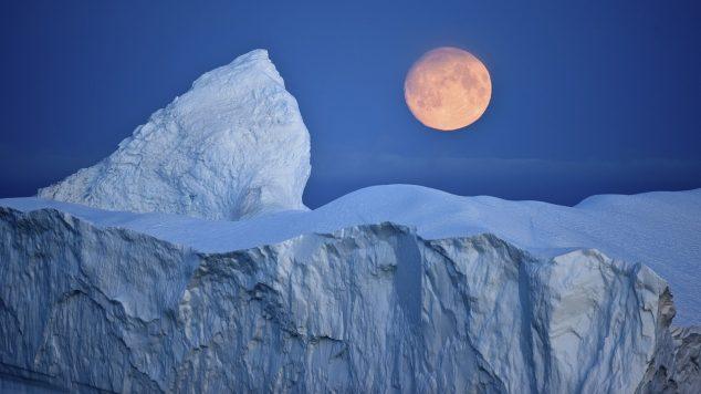 Image of Moon over iceberg