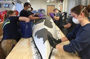 masked students working on canoe