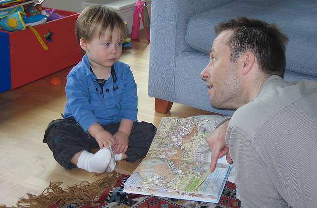 Young boy and father reading book