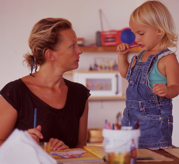 Mother and young child reading book at table