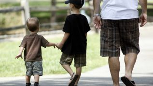 Two young boys walking with Dad
