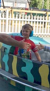 Young boy smiling with headphones on amusement ride