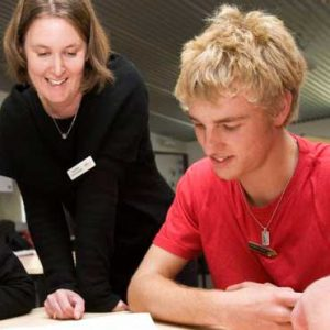 teacher and teen boy at desk