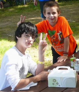 Two boys outdoors signing 'Peace' sign