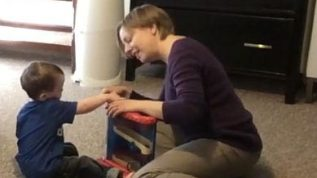Young boy and teacher sitting on floor with toy between them