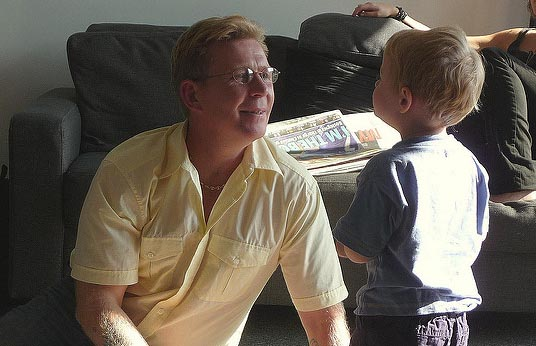 father and toddler smiling at one another