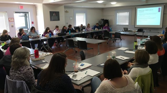 teachers sitting at classroom tables