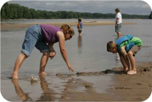Mother and son digging in mud at riversedge