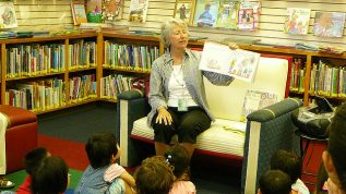 Librarian reading a picture book to group of small children