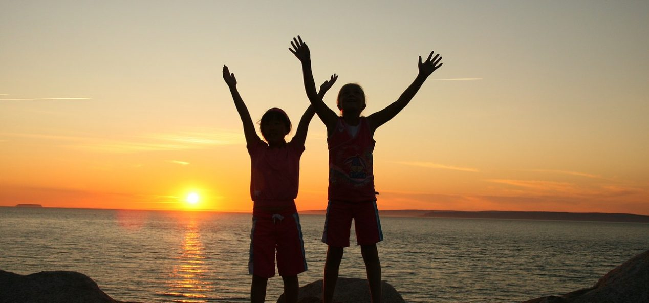 Two young children on beach at sunset