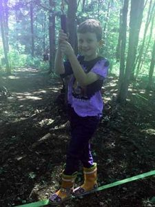 Young boy balancing on low ropes course