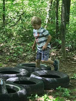 Young boy hopping tires