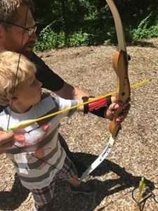 Young boy guided by man to shoot bow and arrow