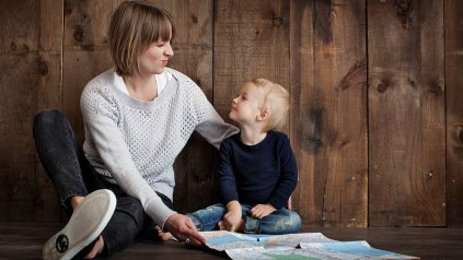 Mother and child sitting on floor looking at each other