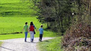 Mother and two sons holding hands walking down a gravel path