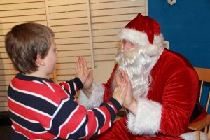 Young boy high-five to Santa