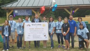 Group of volunteers standing with welcome sign