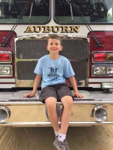 Young boy sitting on firetruck and smiling