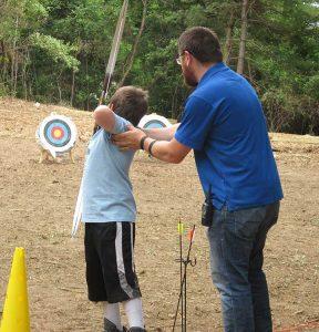 Young boy shooting arrow at target with man guiding him