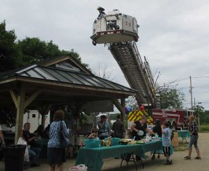 Fire truck with ladder up over picnicing families