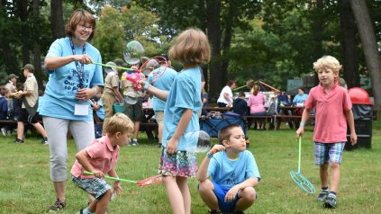 Young children blowing bubbles in field