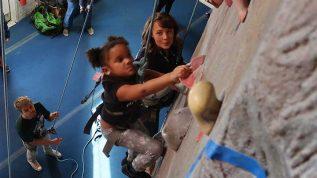 Young girl climbing indoor rock wall