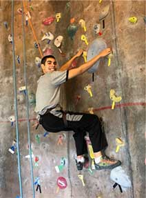 Teen boy smiling from an indoor climbing wall