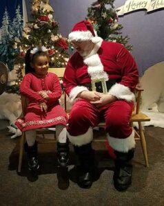 Young girl sitting next to Santa