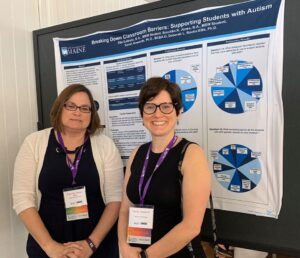 Drs. Howorth and Rooks-Ellis smiling in front of their conference poster