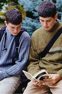 two male students reading together