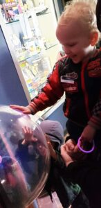 Two young boys touching clear globe, smiling, at Astronomy Center