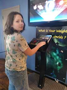 Young boy interacting with astronomy exhibit console