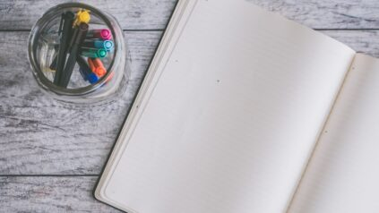 Open journal and jar of colored pens on a table