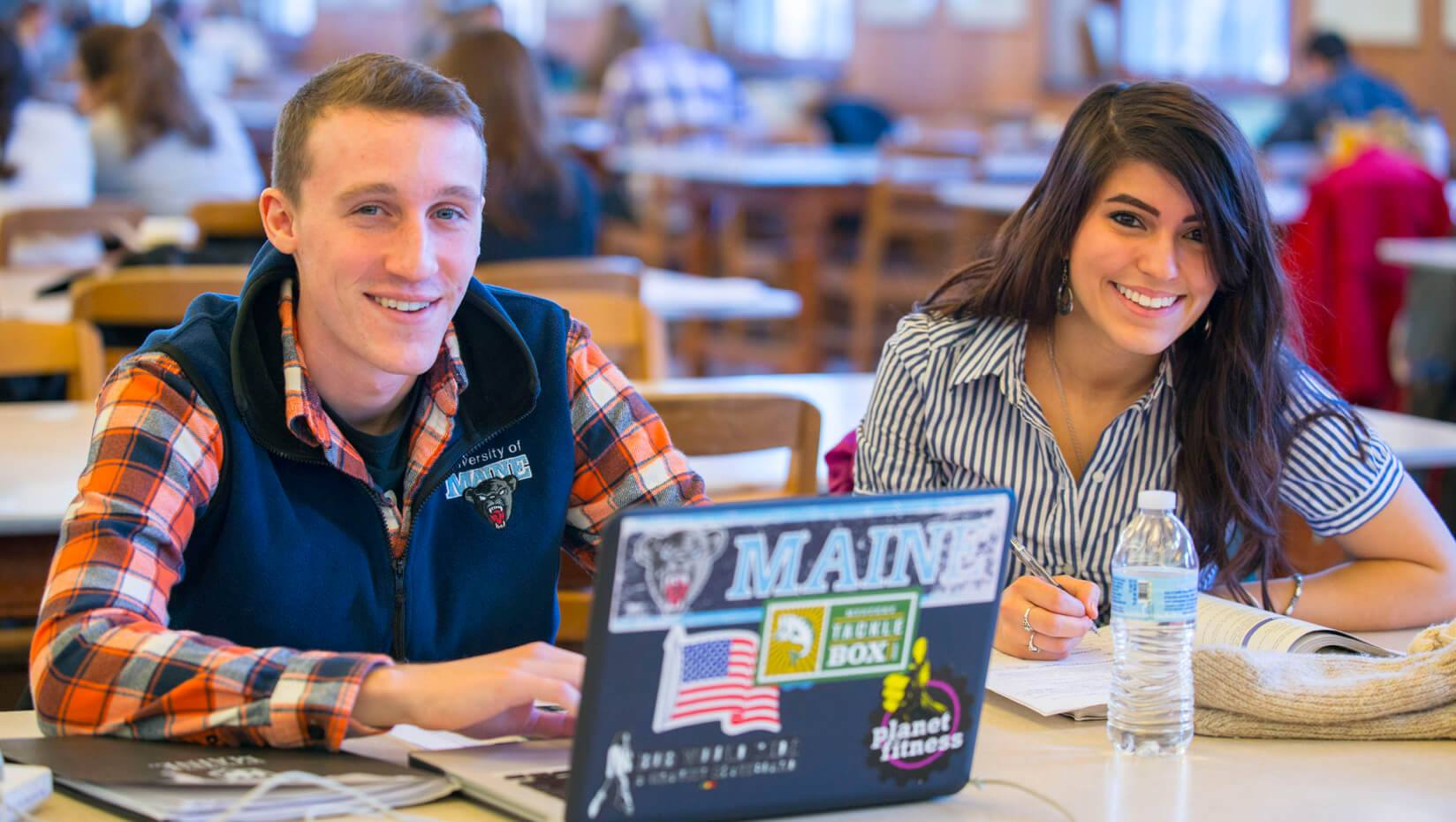UMaine students in Fogler Library smiling with laptop