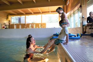 children on pool edge with instructor catching