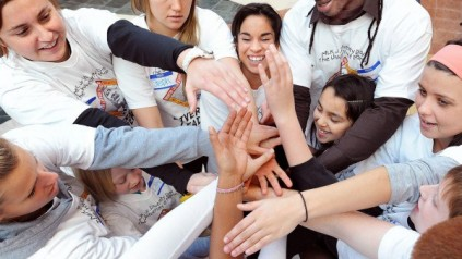 Group of young individuals in matching t-shirts, with their hands interconnected.