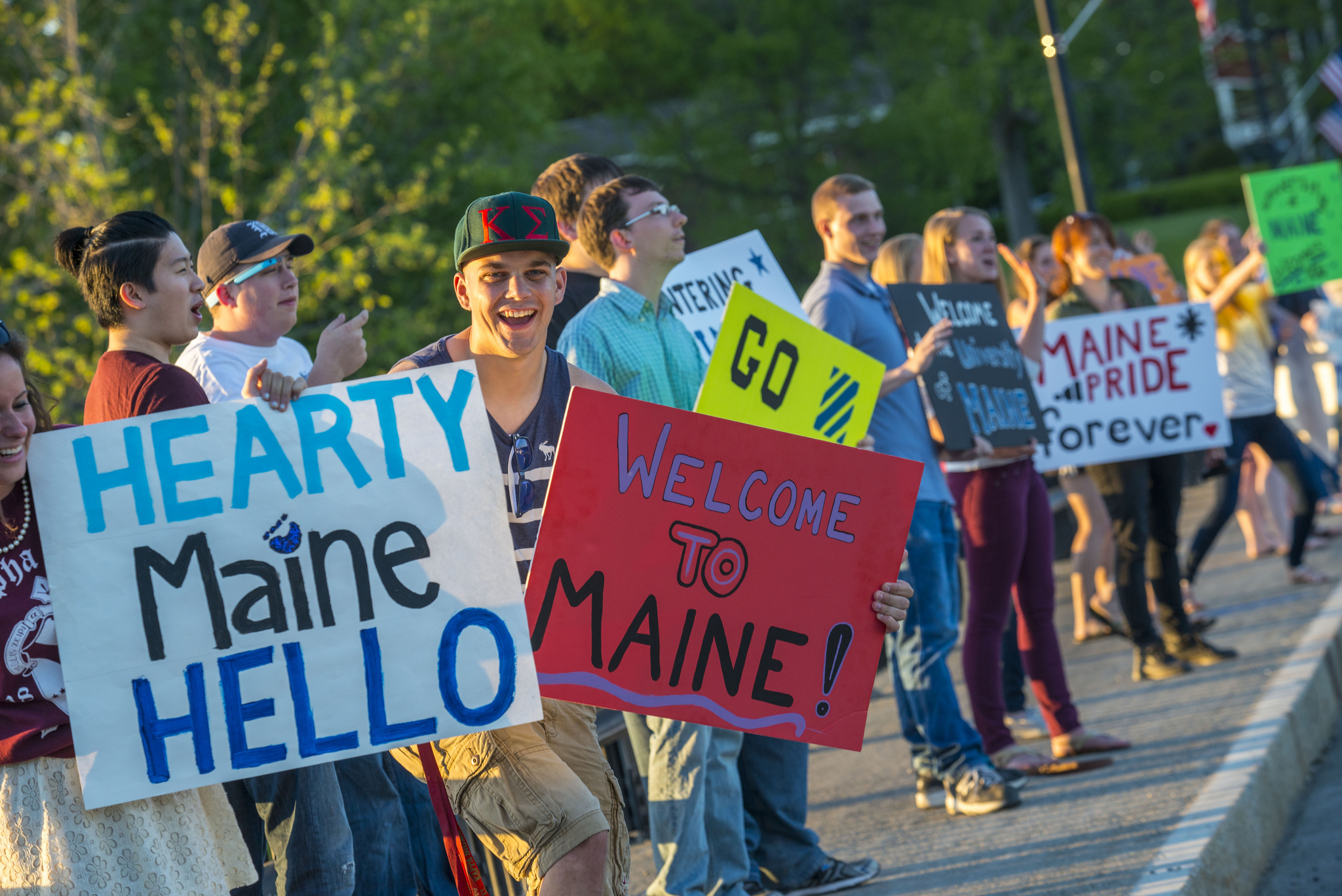 UMaine students with welcome/UMaine spirit signs on Maine Hello.