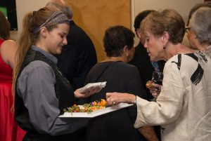 Catering worker handing out appetizers