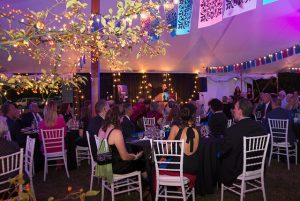 Tented event with people sitting at tables