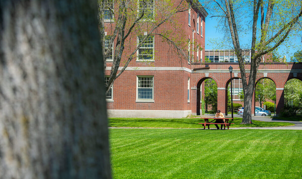 A student sits at a picnic table; Stevens Hall is in the background