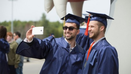 Students at graduation taking a selfie