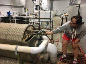 CCAR intern Mei Mei cleaning a drum filter