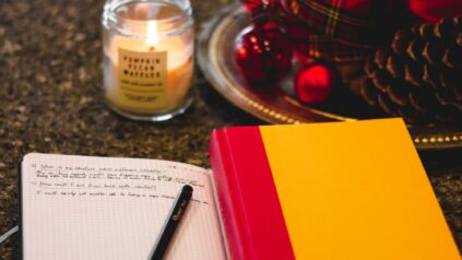 ID a journal open with a scented candle burning