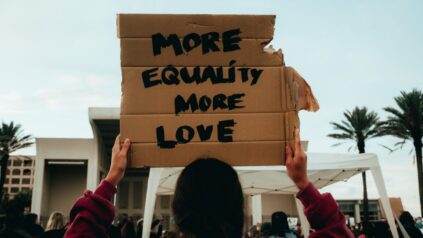"ID a woman in a rally holding a sign saying ""more equality more love"""
