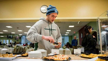 Student putting desserts on his plate at York Dining