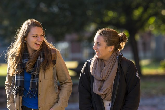 two female students walking on campus in fall