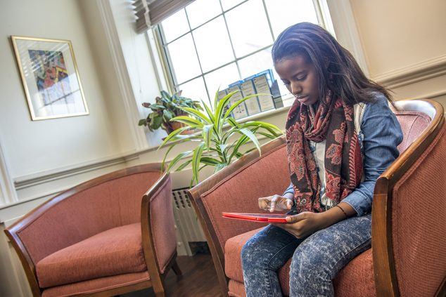 female student in chair on ipad