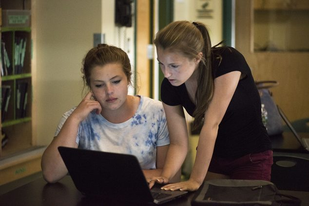 two high school girls looking at computer laptop screen